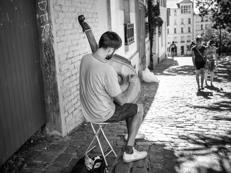 Gatamusikern spelar stränginstrumenten på den Montmartre trottoaren med kringresande par i mellersta avstånd, Paris, sen sommar fotografering för bildbyråer