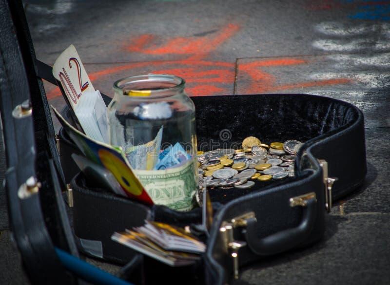 Gatamusikerpengar i olika valutor i gitarrfallet fotografering för bildbyråer