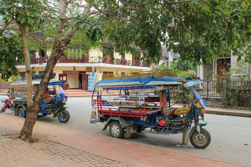 Gatan av den tidigare huvudstaden av Laos, staden av Luang Prabang med byggnader av kolonial fransk arkitektur och populär tuk arkivbild