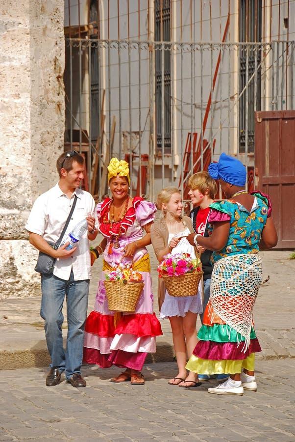 Gatan modellerar i havannacigarren, Kuban som f?r en turist- familj att ta en bild med dem i f?rgglad traditionell kl?nning arkivbilder