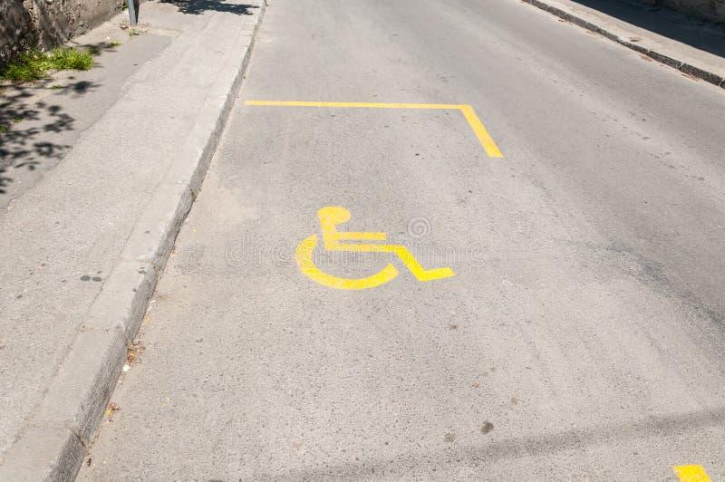 Gataparkeringsplats för det rörelsehindrade folket som kör bilen med gult symbol eller tecknet av den ogiltiga rullstolen fotografering för bildbyråer