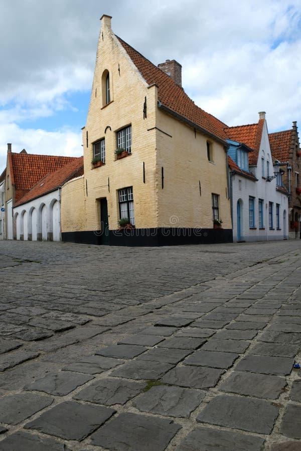 Gataplats i Bruges/Brugge, Belgien med gul hus- och kullerstenstenläggning royaltyfria bilder