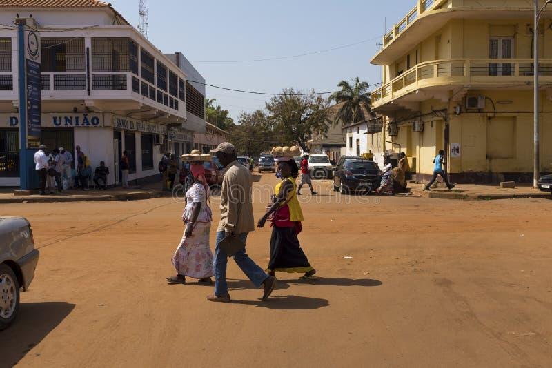 Gataplats i staden av Bissau med folk som korsar en grusväg, i Guinea Bissau royaltyfri foto