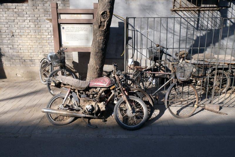 Gataplats med cykeln och mopeden framme av en borggårddörr i Peking royaltyfria bilder