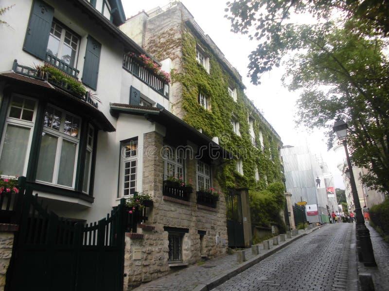 Gataplatsen längs gatan där är boningshus med stenfasader och krullande väggar royaltyfria bilder