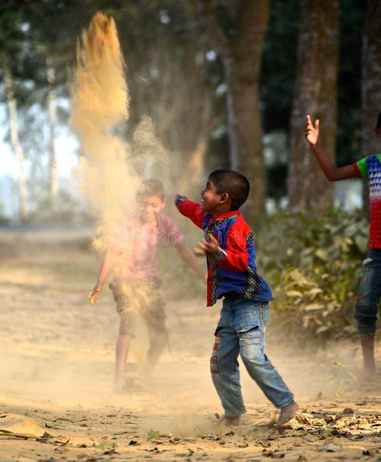 Gatapojkar spelar med sand i Bangladesh royaltyfri bild