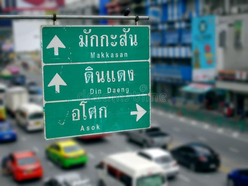 Gatariktningsetiketter med thailändska och engelska texter och pilar till andra ställen i Bangkok royaltyfri fotografi