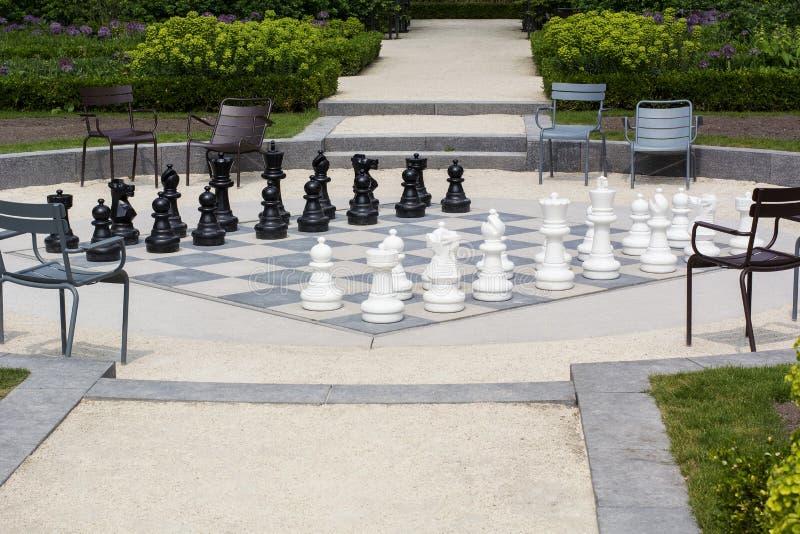 Gataschackbräde med svartvita schackpjäser i parkera royaltyfri bild