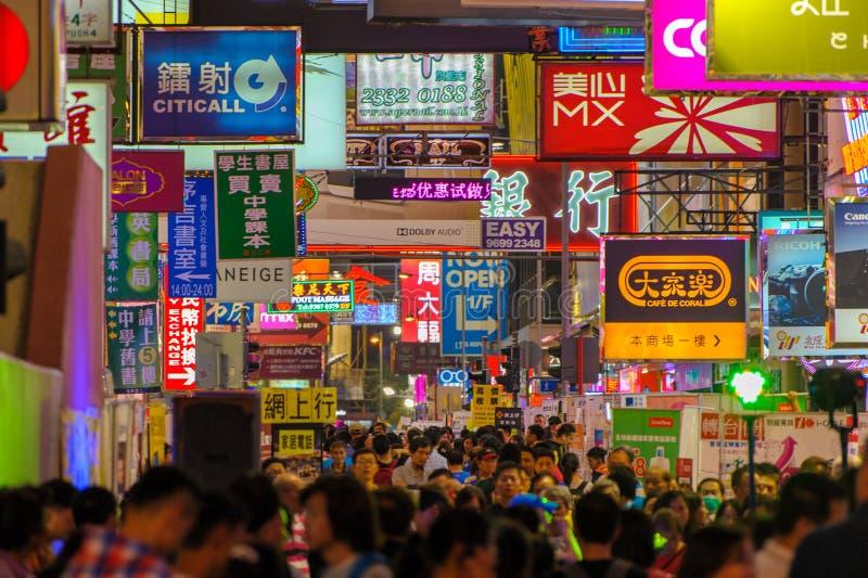 Gatasikt av Hong Kong med många advertizingaffischtavlor fotografering för bildbyråer