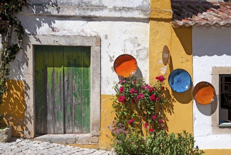 Gatasikt med det gamla huset som visar krukmakeri i Obidos, Portugal royaltyfri bild