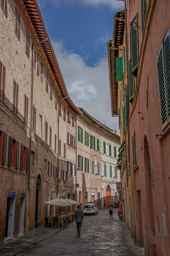 Gatasikt och högväxta byggnader i en molnig dag på Siena royaltyfria bilder