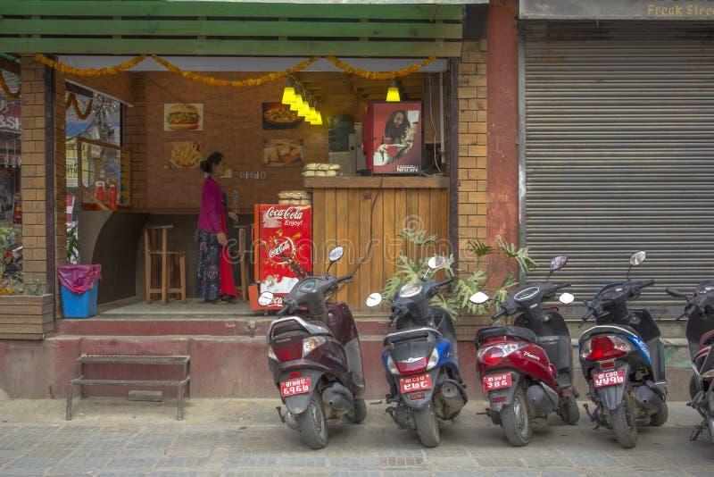 Gatasnabbmatrestaurang med parkerade motorcyklar och en kvinnainsida royaltyfri fotografi