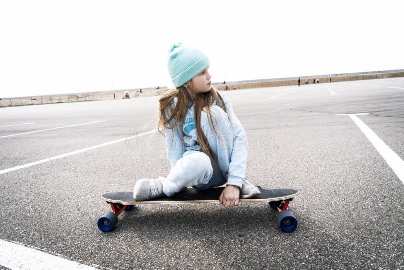 Gatasportar: En flicka i en blå tröja och för lock rullar snabbt på en longboard arkivbilder