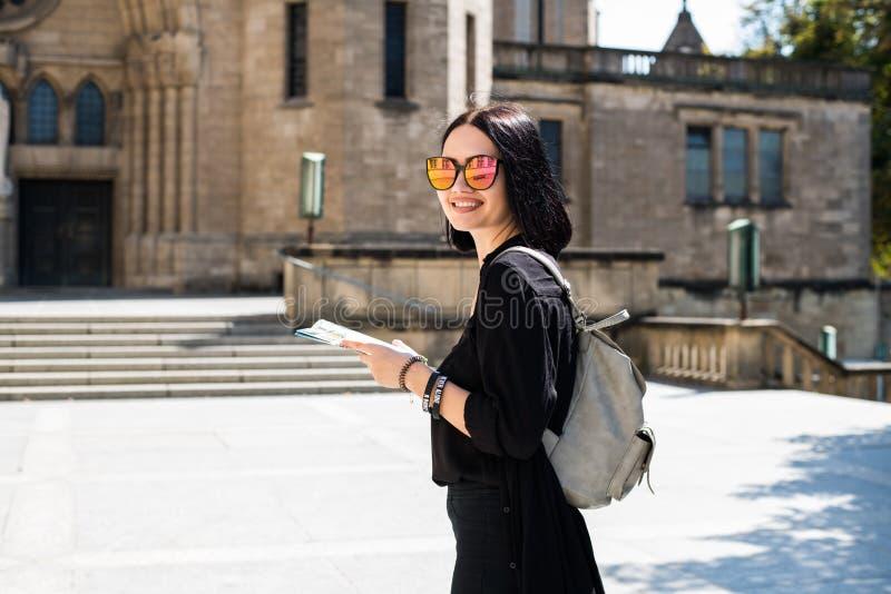 Gatastående av den härliga unga kvinnan som går i stadsgata med ryggsäcken arkivfoto