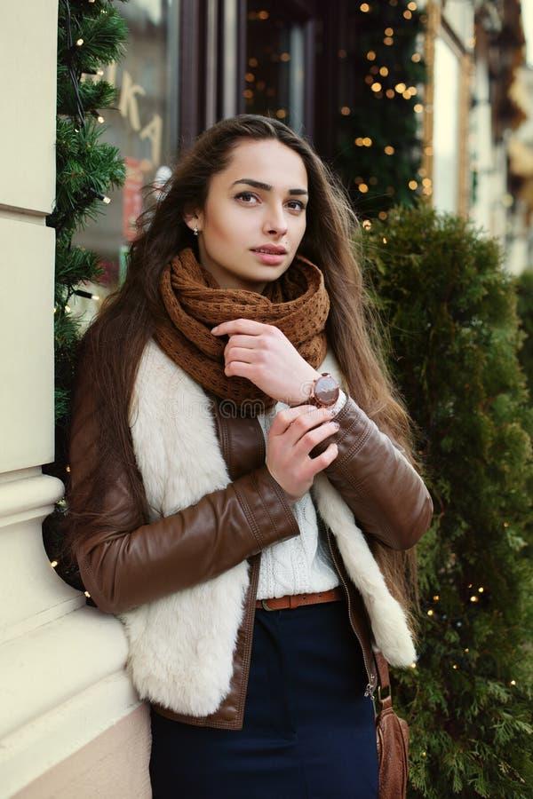 Gatastående av den unga härliga trendiga damen som bär stilfull kläder som går i den gamla staden Modell som ser royaltyfri bild