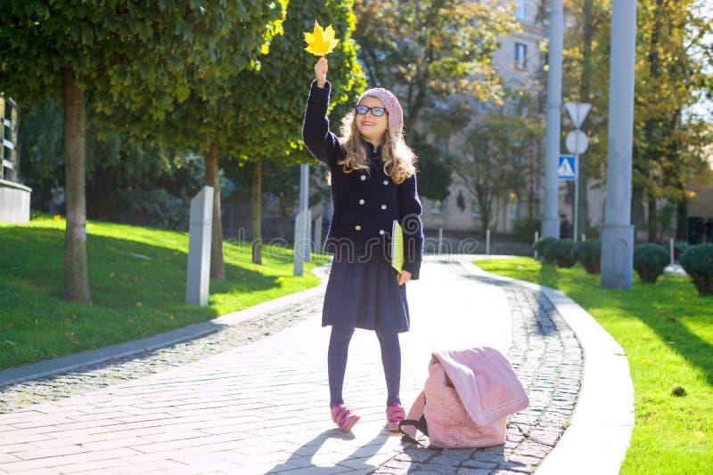 Gatastående av en gullig flicka i exponeringsglas, lag, fransk basker med en anteckningsbok i händer, bakgrundshöststad royaltyfria foton