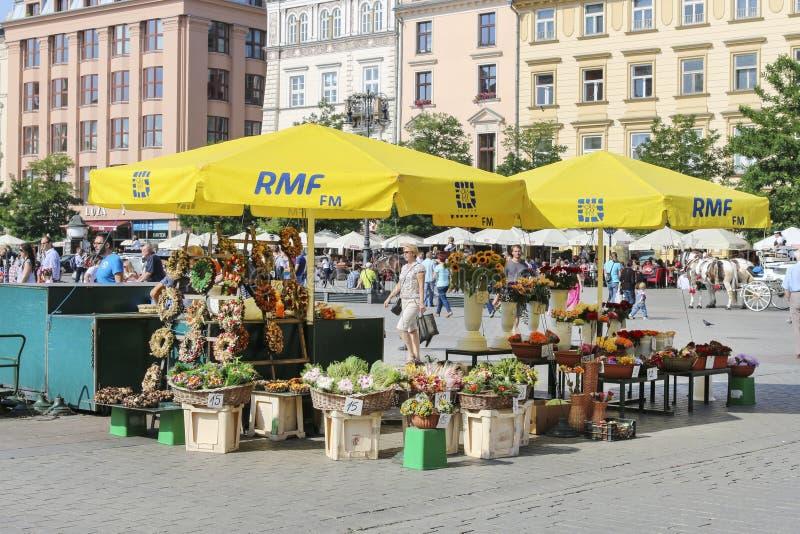 Gatastall med blommor på den huvudsakliga marknadsfyrkanten, Krakow, Pol royaltyfri foto