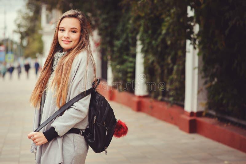 Gatastilstående av den unga härliga lyckliga flickan som går i höststad royaltyfri fotografi