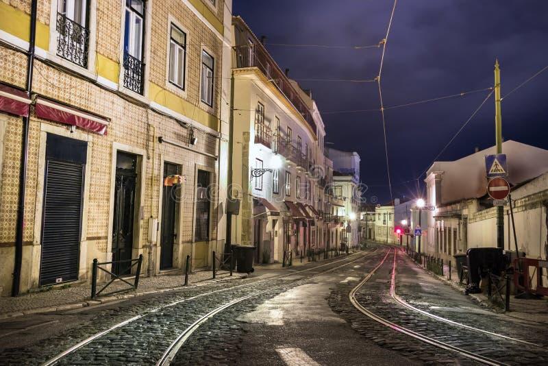 gatatrottoar med spårvagnjärnvägar på en stormig natt som är tom av folk i Lissabon, Portugal arkivbilder