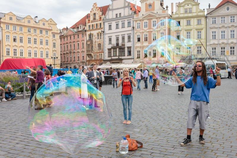 Gataunderhållaren skapar stora bubblor, genom att använda tvåligt vatten, och ett rep i hand och folk har gyckel med det royaltyfria foton