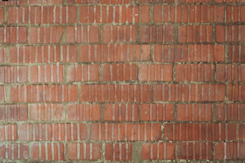 Gatavägg av röda tegelstenar som utföra i relief med de ojämna väggarna royaltyfria bilder