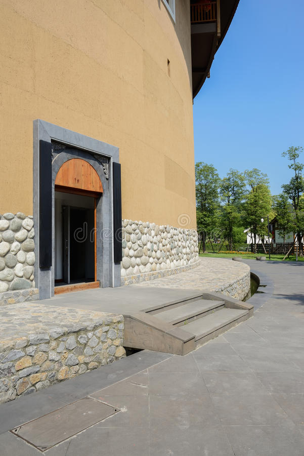 Gate of circular earthed dwelling building in blue sky. The gateway of a circular earthen dwelling building on sunny day,Chengdu,China stock image