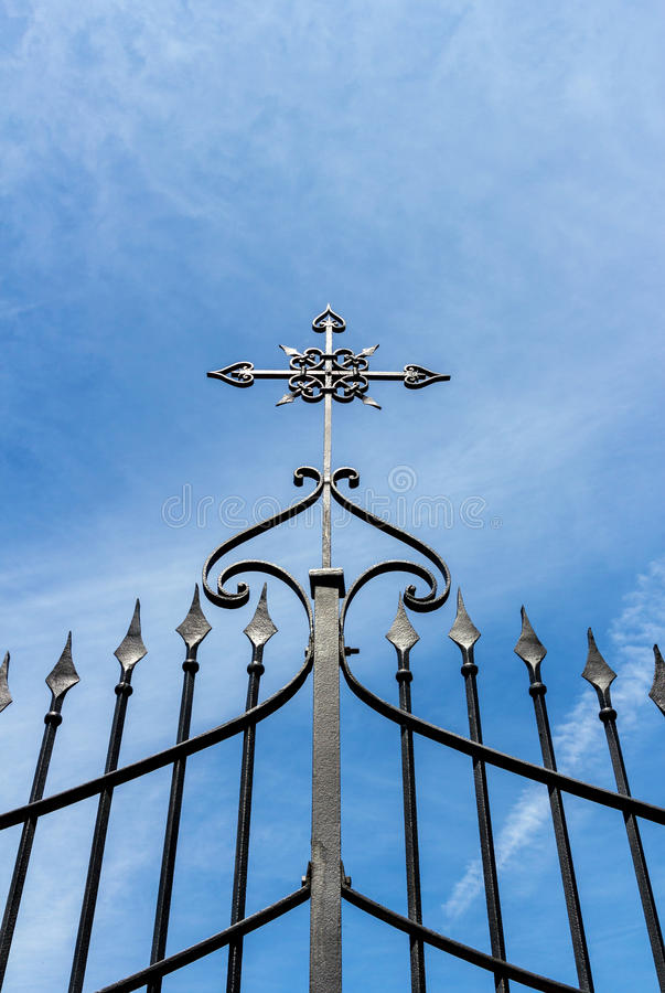 Gate with cross. Wrought iron gate with cross against blue sky royalty free stock photo