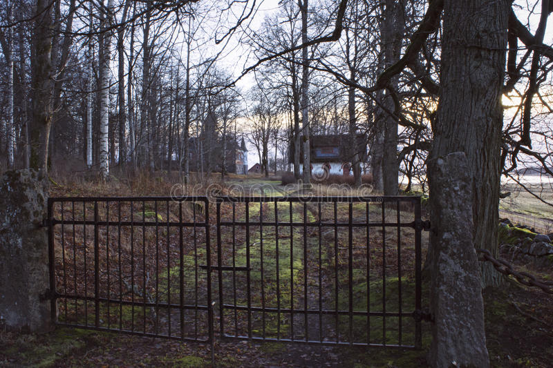 Gate in front of little white cottage in mysterious forest. Gate in front of road leading up to small, old cottage in colourful and mysterious winter/autumn stock photography