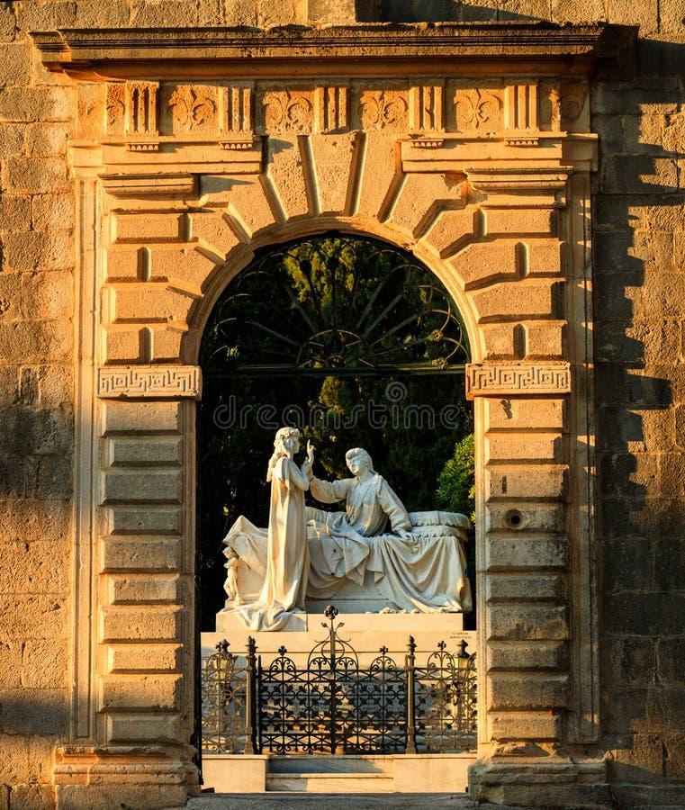 The gate of the Groblje Hrvatskih branitelja cemetery illuminated by setting Sun. stock photography
