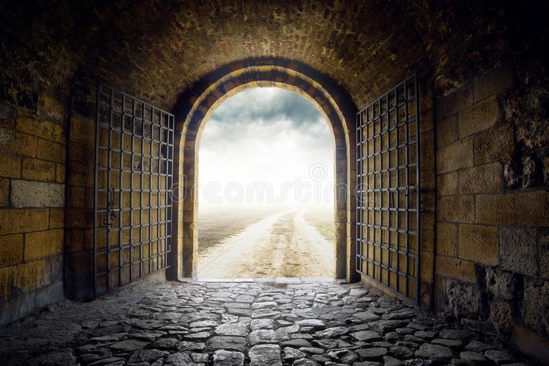 Gate opening to endless road leading nowhere. Old Arch Gate opening to endless country road leading nowhere. Hopelessness and great unknown concept stock photo
