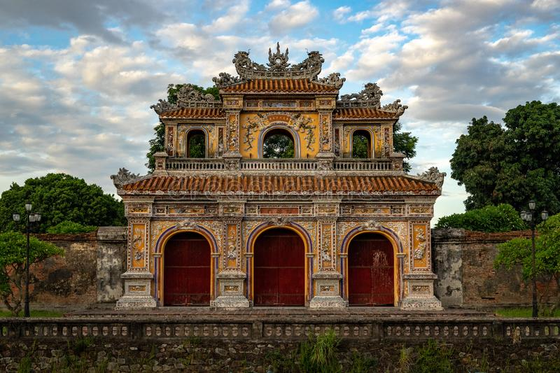 Gate to the Imperial City, Hue. Old historic gate to Imperial City in Hue, Vietnam. Photo is taken with sunset and partly cloudy sky. Around gate is green forest stock image