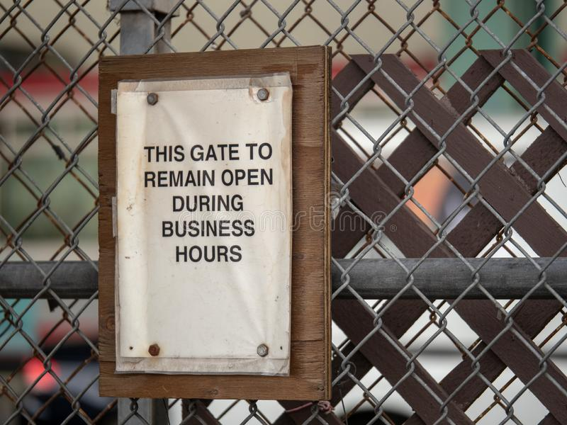 This gate to remain open during business hours paper sign on fence. This gate to remain open during business hours paper sign hanging on fence royalty free stock images