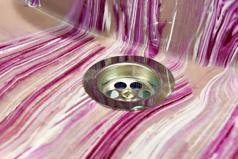 Gaten voor drainagewater in badkamers roze gootsteen stock afbeelding