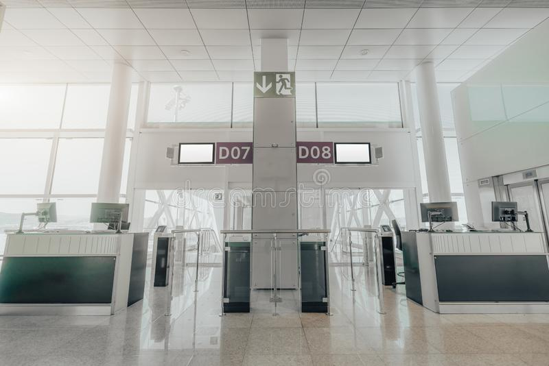 Gates in an airport terminal. Wide-angle view of empty gates of a modern airport terminal with computer monitors on the counter desks, information screens on the stock photo