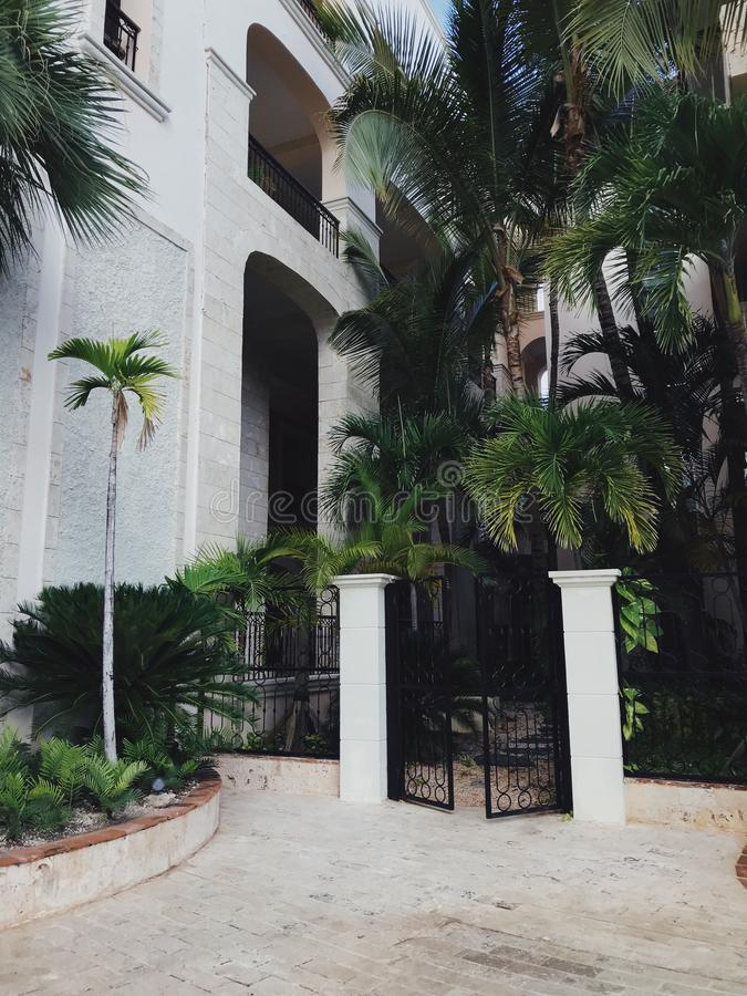 Gates to luxury residence in cap Cana. Near Atlantic Ocean in Dominican Republic. Facade is white. Lots of palm trees and bushes growing near the residence stock photography