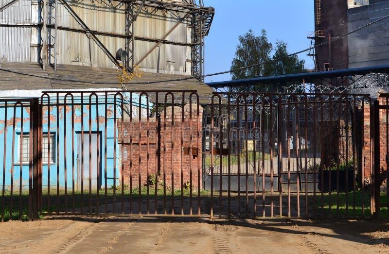 Gateway aan een beperkt gebied omheining met prikkeldraad tegen een blauwe hemelachtergrond Veiligheidsconcept, verboden grondgeb stock afbeelding
