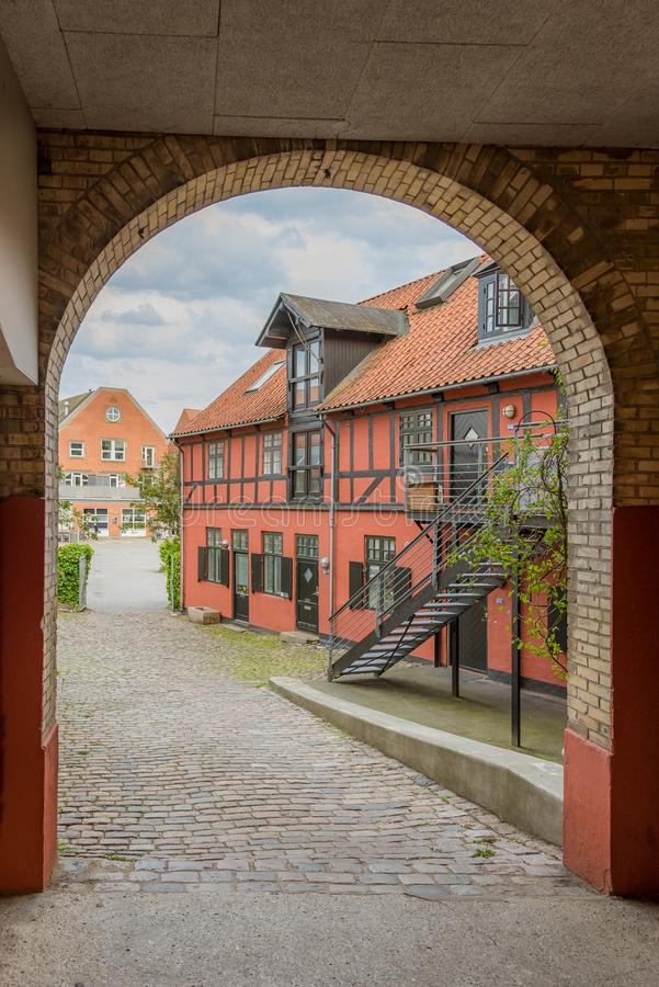 A gateway with cobble stones into a yard with an ancient, red, half-timbered house in Svendborg. A gateway with cobble stones into a yard with an old half royalty free stock images