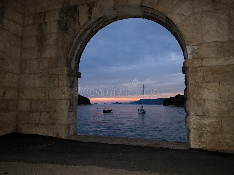 Gateway to the a seascape. A brick and stone gateway is seen giving a peek into a seascape comprising of blue water, two boats, islands under a nlue sky during stock photo