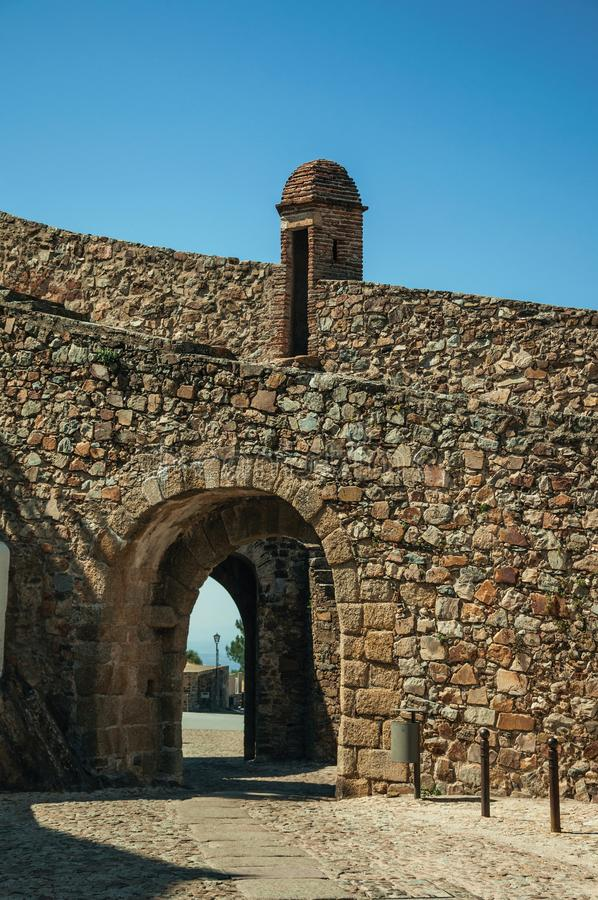 Gateway in wall made of rough stone with watchtower stock image