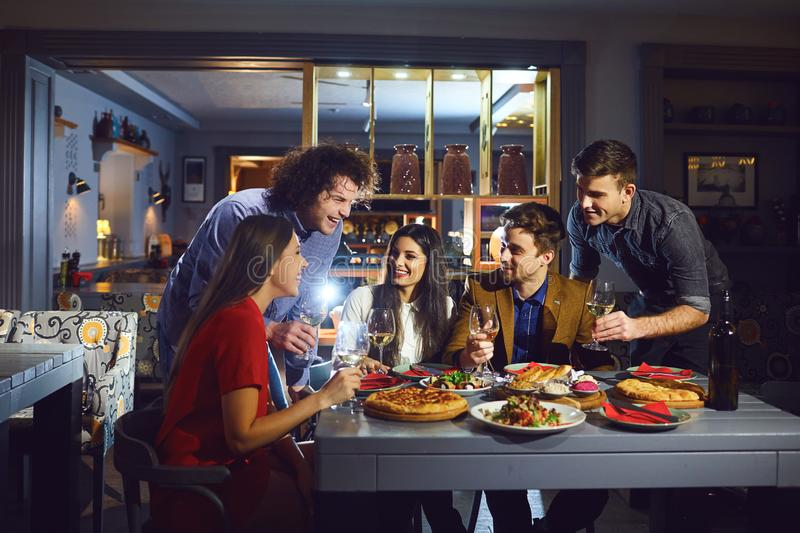 Gathering friends in the restaurant in the evening. stock photography