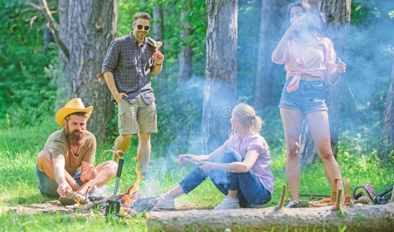 Gathering for great picnic. Friends meeting at meadow to hang out and prepare roasted sausages snacks nature background. Join summer picnic. Company having fun royalty free stock image