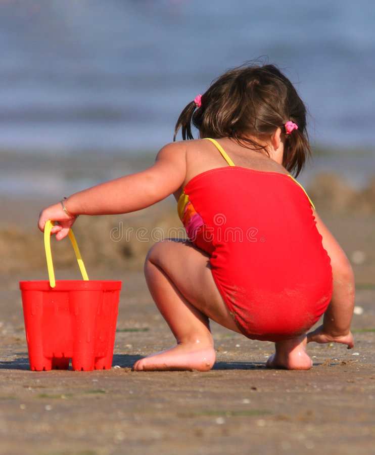 Gathering The Shells. Little girl wearing a red swimming costume, holding a red bucket in her hand and gathering shells on the beach in summer. Rear view royalty free stock photos