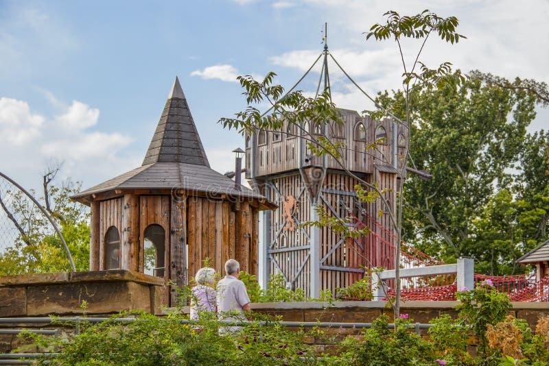 Gatherning地方的告密者峰顶-独特的社区河边区公园-资深夫妇在看城堡剧场的桥梁站立 库存图片
