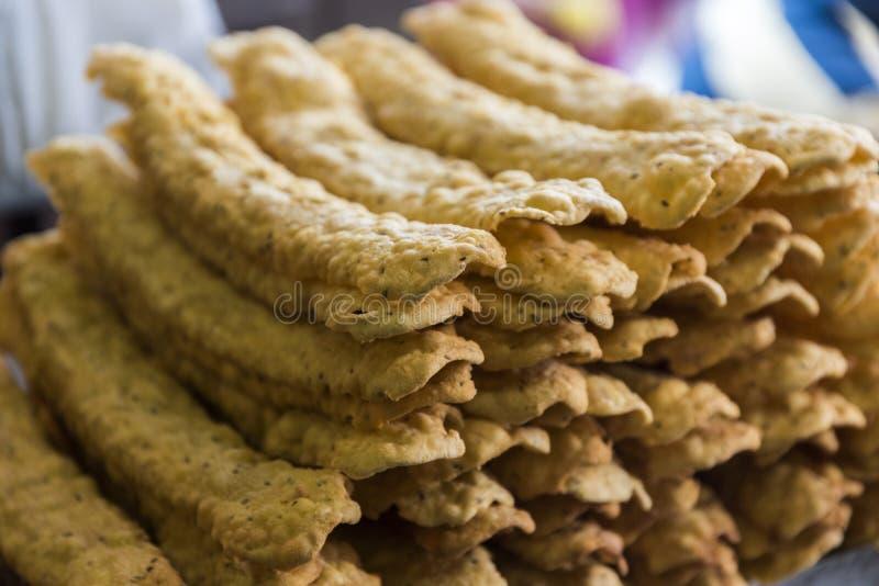 Man Frying Ganthiya / Gathiya Indian Namkeen - tea time snack on roadside in Nathdwara Rajasthan India. Gathiya are deep fried Indian snacks made from chickpea stock photo