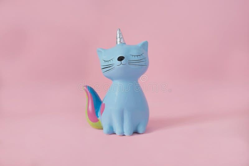 Gatito de cerámica Korn del moneybox del juguete del recuerdo azul con la cola colorida del arco iris con los ojos cerrados y el  imágenes de archivo libres de regalías