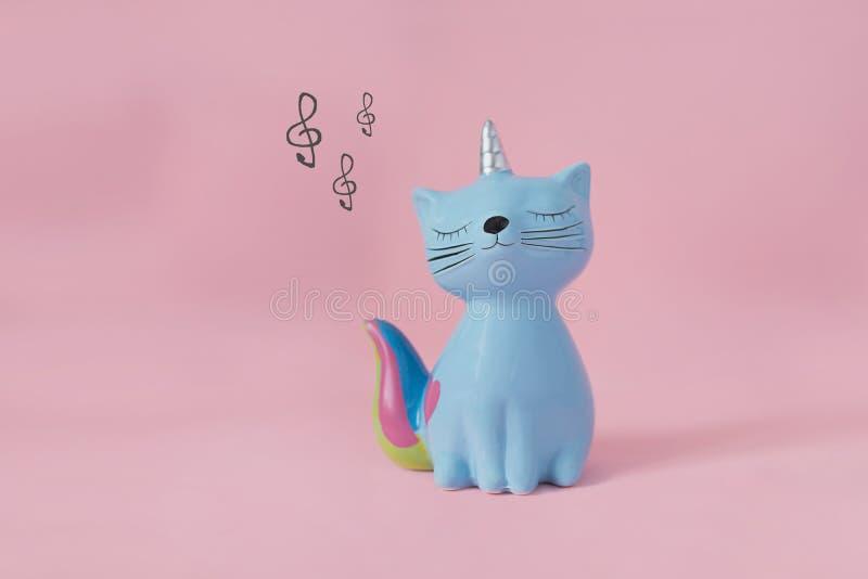Gatito de cer?mica Korn del moneybox del juguete del recuerdo azul con la cola colorida del arco iris con los ojos cerrados y el  foto de archivo libre de regalías
