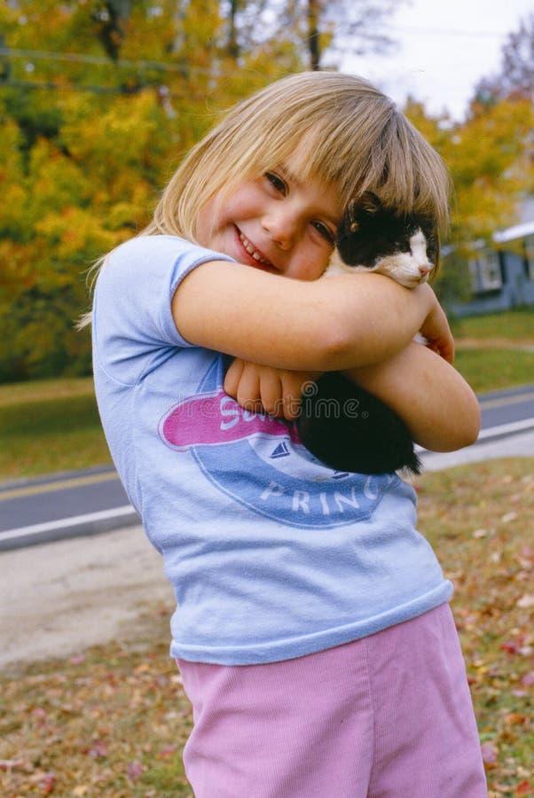 Gatito de la explotación agrícola de la chica joven imagenes de archivo