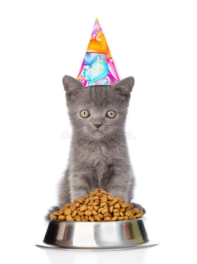 Gatito en el sombrero del cumpleaños que se sienta cerca de un cuenco de comida aislado encendido imágenes de archivo libres de regalías