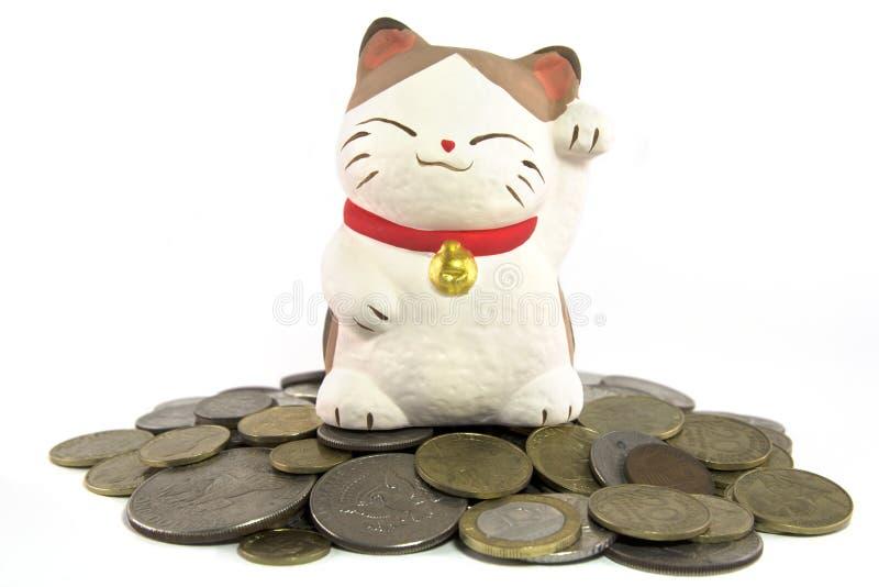 Gato afortunado en el montón de monedas fotografía de archivo
