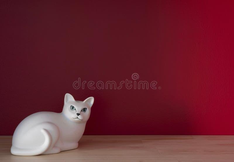 Gato cerâmico branco e cacto pequeno numa prateleira fotografia de stock royalty free